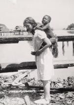Margaret Mead carrying a Manus girl, probably Piwen on her back, 1928