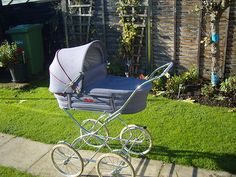 GREY FABRIC SILVER CROSS PRAM WITH RED TRIM |