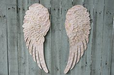 Shabby chic set of large hand painted metal angel wings. Done in soft pink and accented in gold with a protective coating. They each have 3 sawtooth hangers on the back and can be hung several differe