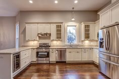 Photo gallery of remodeled kitchen features CliqStudios Dayton Painted White cabinets with peninsula seating crown molding and undercabinet lighting