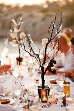 Like the use of the branches, white instead of black, as well as the crystal beads, just with more flowers.  Makes it modern though and look cool without a TON of flowers required.  More than this picture though.