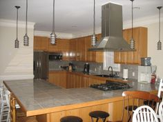 This Cavaliere island #rangehood looks amazing in this customer's kitchen. We also like the accent the hanging lights add to the space.