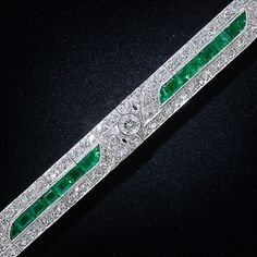 gorgeous glistening line of rich, bright green emeralds is the main attraction of this exquisite and exemplary bracelet, finely crafted in platinum (and diamonds of course) during the zenith of the Art Deco period - circa 1925. The beautiful line of emeralds is punctuated by five sparkling diagonal diamond designs and is bordered on each side by twinkling Swiss-cut diamonds. Yummy!