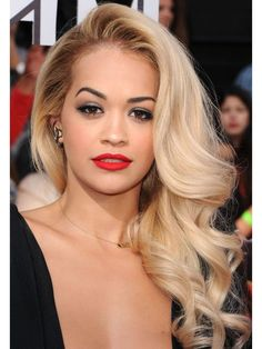 To give your blowout major bounce, use a round brush to dry two-inch sections at a time, pinning each section into barrel curls while they cool. When you let them down, you'll have big, glam curls! Part hair on the side, and tease the roots to get Rita Ora's flirty down 'do.