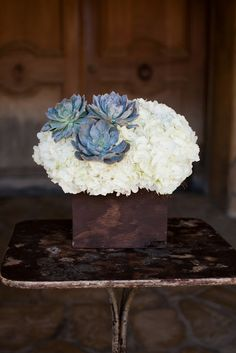 Wooden box filled with white hydrangea and succulents