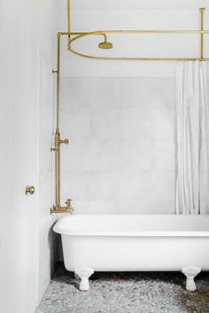 White on white tub in bathroom with brass plumbing fixtures