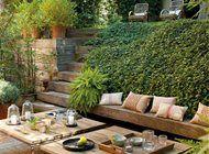 Jardín con mesas y banco de madera