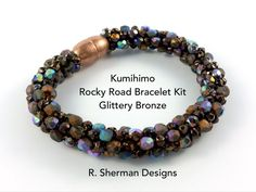 Complete kit contains nearly everything you need to create the Kumihimo Rocky Road Bracelet in Glittery Bronze, and featuring Fire Polished beads  Techniques used: 8 warp cord Kongo Gumi (beaded round braid) Braiding around a core. Prior experience with Kumihimo braiding with beads is essential, but if you havent previously used a core in your braiding, the included pattern provides instruction. Its easy!  Kit includes: - Complete tutorial with bead loading pattern, tips, and finishing…