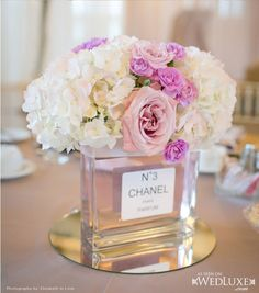 Chanel Perfume bottles add a touch of femininity to the centerpieces. Great idea that's unique! !