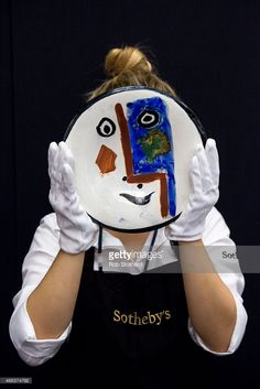 A Sotheby's employee holds Pablo Picasso's 1963 plate 'Visage no. 193' at Sotheby's auction house on March 13, 2015 in London, England. A selection of approximately 150 vases, pitchers, plates, bowls and other ceramics, valued from £800 to upwards of £50 will be auctioned at Sotheby's on 18 March.