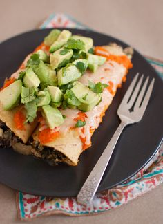 Hearty, vegetarian black bean enchiladas that make use of pantry and freezer ingredients. Top with cilantro and avocado for a fresh and vibrant meal.