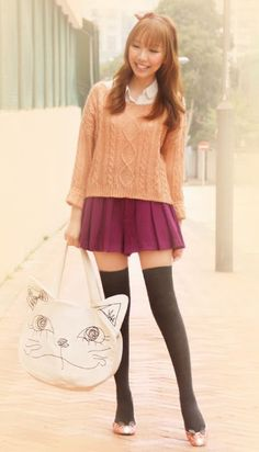 The look is great, little pleated burgundy skirt paired with black stockings and orangee sweater, and that big catface bag, cool ! Japanese Fashion