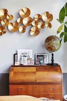 """House tour: inside a young couple's vibrant Dutch townhouse: From behind the kitchen counter — designed to resemble an once desk, in a warm walnut with accents of petrol green — all corners of the living room are visible, including the sunken lee uil (conversation pit), with its custom velvet sofas and dramatic ceiling- high bookcases. """"A 1970s setting like this has been on our wish list for a long time,"""" says Urbanus. """"It works perfectly with this house."""""""