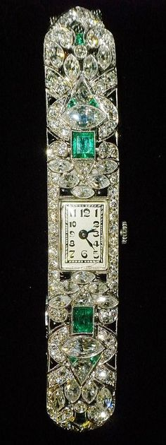 Art Deco Diamond and Emerald Bracelet Watch. The watchcase and bracelet is made of platinum and is set with approximately 5.50 carats total weight of diamonds and accented with approximately 1.25 carats total weight of natural emeralds. The mesh band is made of 14k white gold.