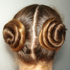 """I tend to wear my hair parted like this a lot. But I twist my hair and swirl it around to make buns on each side. And I wear two long hanging twists in the front as """"bangs""""."""