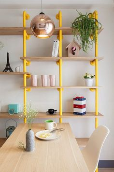 linda sala de jantar luminária cobre e estante amarela