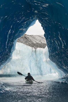 Kayaker Paddles Through An Ice Cave Amongst Giant Icebergs Near Bear Glacier In Resurrection Bay Near Seward, Alaska