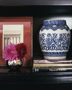 3 objects - picture (colorful mat), flowers in shiny vase and blue & white jar on top books