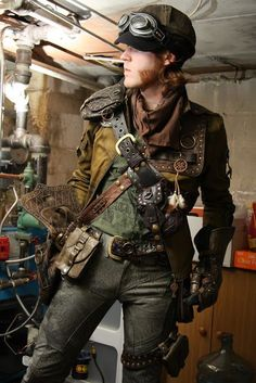 Steampunk Lad with mutton chops - A utility belt worn across the chest AND around the waist, gauntlet, goggles, leather messenger bag, hat, pants, t-shirt. Modern men's steampunk clothing  - For costume tutorials, clothing guide, fashion inspiration photo gallery, calendar of Steampunk events, & more, visit SteampunkFashionGuide.com