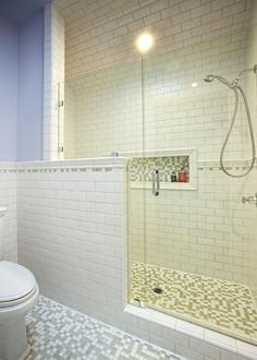 White subway tile sheathes the wall and shower in this traditional bathroom, while square mosaic tiles add punch underfoot. Pale blue walls continue onto the ceiling for an unexpected touch.