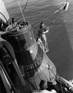 On April Grissom dons the new Mercury spacesuit as he awaits participation in the emergency water egress training. He stands near the mockup Mercury capsule on the deck of the ship.