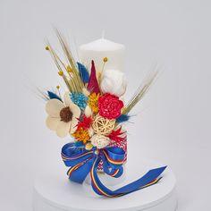 Lumanare de botez nemuritoare cu aranjament floral realizat pe o parte, alcătuit din flori, gheme colorate si o selectie de plante stabilizate si flori uscate in cromatica alb, rosu, galben si albastru, cu panglici din saten in culorile tricolorului, pentru o nota traditional romaneasca.  Avantajele unei lumanari cu flori nemuritoare este acela ca are proprietati decorative ce nu dispar, florile raman la fel de frumoase, nu isi pierd stralucirea culorilor si nu li se scutura petalele. Christening, Birthday Candles, Wedding, Decor, Casamento, Decoration, Decorating, Weddings, Dekorasyon