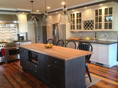 white cabinets with dark grey quartz counter. dark grey or black island with butcher block counter