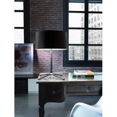 A modern table lamp made in steel with a matte black finish. A slender stem features a four legged base for excellent stability. Comes complete with a black shade. We love this in a contemporary bedroom or living room.