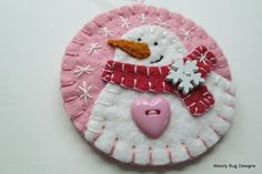 This is a brooch ! This is also an ornament ! This white wool felt snowman is handstitched onto a soft pretty pink wool felt background. The coral pink wool felt scarf has a big wooden snowflake button hand stitched on. The snowman boasts a big pink heart shaped button. The last