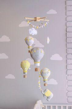 Bebé móvil de globos de aire caliente para la decoración de su dormitorio. Perfecto para un viaje de niños del tema! Cada globo pequeño es hecho de la tela, cose, rellena y adornado en mi estudio a mano. Pequeños botones, pompones, lazos atados de mano y banderas del empavesado adornan los globos. El pequeño elefante puede tener una pequeña corona o sombrero del partido. Los globos tienen canastitas 3D impresos para un globo de aire caliente de aspecto natural. Puede personalizar una de las…