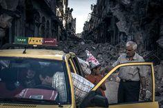 Sergey Ponomarev pour le New York Times -La Syrie d'AssadQuartier d'Al-Khalidiya, Homs, Syrie, dimanche 15 juin 2014. Abu Hisham Abdel Karim et sa famille chargent leurs affaires dans un taxi. Spectacle étrange, des taxis circulent dans les rues désertes, parmi les décombres, pour aider les familles à récupérer ce qui reste de leur maison.