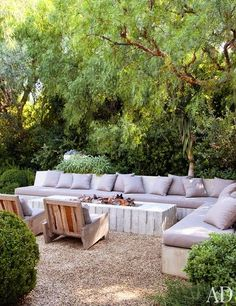 How inviting does this outdoor seating look? Love the modern fire pit and seating surrounded by lush green. The gravel hardscape not only provides a no-water area, but also allows rain water to permeate into the ground.