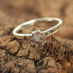 Silver ring with rough diamond solitaire setting and pave set diamonds on either side