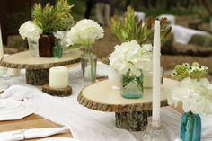 déco mariage champêtre - chemin de table blanc, chandelles et de petits arrangements d'hortensias sur des rondelles de bois