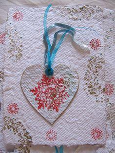 Postal navideña realizada con papel artesanal hecho por nosotras. Estampado de motivos navideños en rojo y azul turquesa. El corazón se puede quitar de la postal para adornar cualquier rincón.