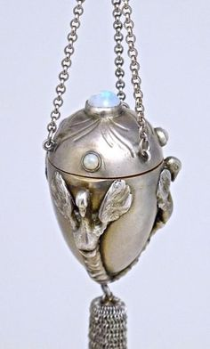 c1900 Boucheron-Paris, Art Nouveau pendant scent bottle, sterling silver amphora, 3 applied birds, mesh tassel, hinged cap with 4 opals, gilt interior, crystal vessel and stopper, hung from silver chains joined by a fire opal. Boucheron mark, 2 silver marks, silversmith's mark. Pendant 1 5/8 in. Total length 23 in. *Previously owned by: Louise Vava Lucia Henriette Le Bailly (Lou Lou) de la Falaise – daughter of Schiaparelli model Maxime, and Count Alian Le Bailly de La Falaise.