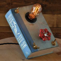 """Not exactly a bottle, but a recycled book! Love the red valve - it actually turns the light on and off! Very submariner-like. Gives new meaning to the term """"book light. Antique Lighting, Industrial Lighting, Kitchen Lighting, Lampe Tube, Book Lamp, Steampunk Lamp, Pipe Lamp, Lamp Design, Lighting Design"""