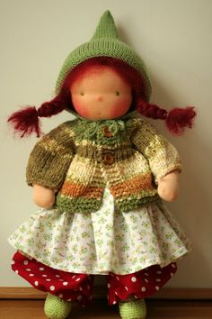 Hand-crafted doll according to Waldorf pedagogy.  Moira is 16 (40 cm) Waldorf doll. Her head is sculpted in the traditional Waldorf style; her eyes and mouth are hand embroidered. Shes made of 100% cotton jersey from Netherlands . Her body is stuffed with cleaned and carded organic sheeps wool. Her hair is made of super soft fluffy mohair. Her cheeks are blushed with fully harmless beeswax crayon.  The cardigan, the hat and the slippers are hand-knitted by me using high quality cotton bouclé…