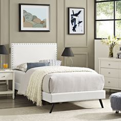 Phoebe Twin Vinyl Platform Bed With Round Splayed Legs In White - MOD-5607-WHIDescription :Accelerate your bedroom decor with the Phoebe Platform Bed. Made with a solid wood frame upholstered in vinyl, Phoebe features tapered wood legs, plastic foot glides, stylish headboard, and ten sturdy wood slats with a centered supporting bar and two support legs for enhanced stability. Due to the wooden slat support system, the use of a box spring is unnecessary. Phoebe supports memory foam mattresses…