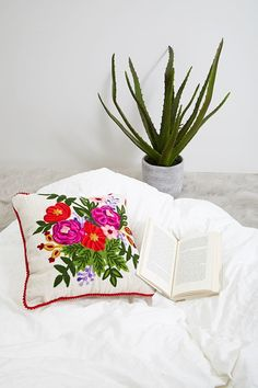 This pillow by Karma Living™ features an intricate floral design intended to bring light and color into your home.