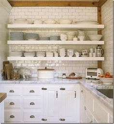 classic. open shelving over tiled wall, marble counter-tops, underset stainless-steel sink.
