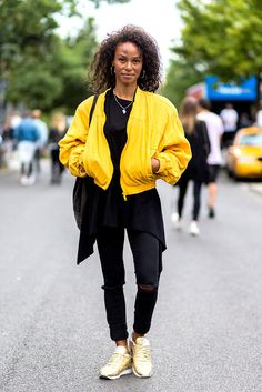 Street styler Maddy Grace brightens up the Berlin scene in a yellow bomber jacket and gold Reebok trainers, but a black dress and black ripped denim jeans keeps it all in check