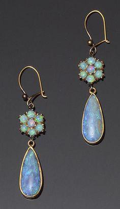 A pair of opal earpendants  Each pear-shaped cabochon opal drop below an opal flowerhead cluster surmount, on wire fittings, length 4.9cm.