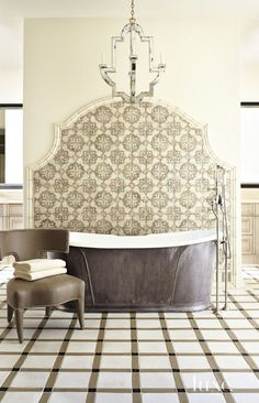 Tile from Craftsman Court Ceramics provides an elegant backdrop for the master bathroom's Devon & Devon soaking tub with a pewter base, purchased at Clyde Hardware Co.