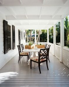 The Best Beach Houses Around the World Tucked Away Black shutters and chairs occupy a sunbleached wrap around veranda, surrounded by luscious palms. An outdoor dining area on a porch (Source: Lonny) Outdoor Dining, Outdoor Spaces, Outdoor Decor, Dining Area, Dining Rooms, Indoor Outdoor, Dining Table, White Porch, Outside Living