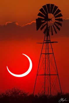 The ultimate engine, the Sun, seen during a Solar Eclipse in Bledsoe, Texas photographed alongside a windmill.