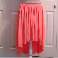 """America Eagle Outfitters, High~Low Hem Skirt America Eagle Outfitters Orange, Adorable High~Low Hem Skirt. This Medium Size Skirt is is Great for the Poolside or Can Easily be Dressed up with a White Top and Wedges. Has an Easy, Purple Colored Stretch Waistband Fit that measures 27"""" Laying Flat and  34"""" Gently Stretched. Has long Flowy Pleats and its made with Polyester & Viscose Fabric. This Skirt is in Excellent Condition. This Color and Style is the Perfect Piece to Wear while Showing Off…"""