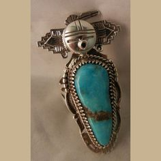 #Ring featuring long brown-matrixed turquoise stone set in sterling silver bezel and topped by a an intricately stamped maiden wearing tableta and feather by #Navajo artist Bennie Ration.