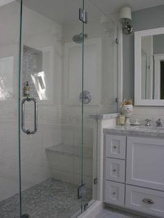 shower stall. Glass door with bronze fixtures. Marble floor tile, subway wall tile. Vanity in graphite.