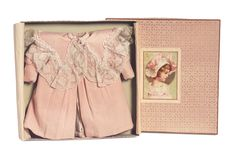 """French Bebe Coat in Original Presentation Box  To fit about size 6 or 7 Bebe Jumeau. Of rose peach soft flannel the coat features a fitted yoke hidden under wide Bertha collar with 2"""" generous ruffled lace trim,Juliette style sleeves,box-pleated front. The coat is presented in its original store box with decorative paper covers and lithograph of young girl in coat and hat.  Circa 1890"""